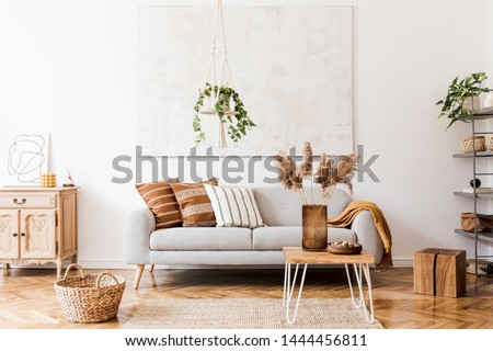 The stylish boho composition at living room interior with design gray sofa, wooden coffee table, commode and elegant personal accessories. Honey yellow pillows and plaid. Cozy apartment. Home decor