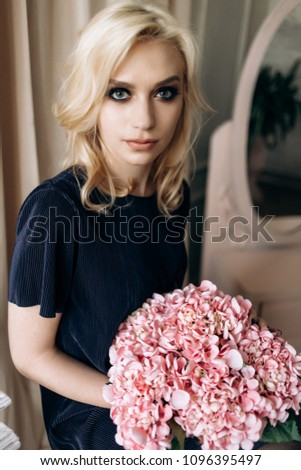 Stock Photo The stylish girl sits on the ladder and keeps flowers