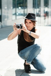The stylish girl student photographs with the retro styled mirrorless digital camera. City travel scene