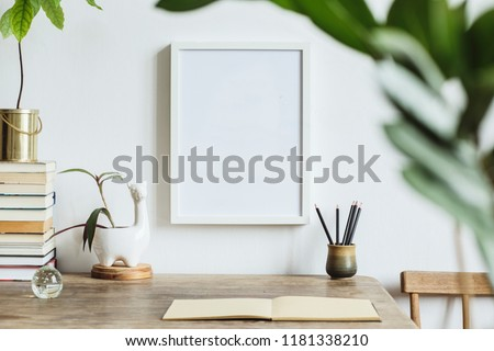 The stylish interior with mock up photo frame, leafs, avocado plant, books, notebooks and lama pot.. The minimalizm concept of space.  Stok fotoğraf ©