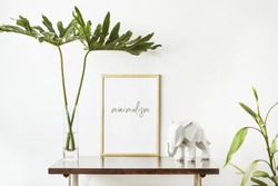 The stylish interior with mock up poster frame, leafs and elephant sculpture. The minimalizm concept of space.
