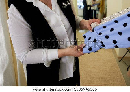 The stylist shows the texture and fabric of the two blouses.Seller demonstrates the quality of clothing.