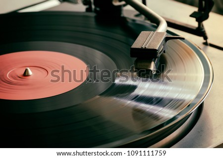 The stylus of the vinyl analog player is in contact with the surface of the rotating LP. Close up. Selective focus.