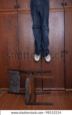 The suicide hung up at a wall case under which the chair lies