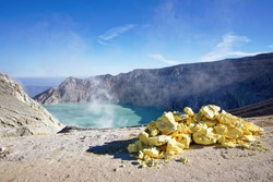 The sulfuric lake of Kawah Ijen vulcano in East Java with sulfur stone in foreground, Indonesia