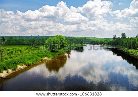The summer clouds drifting over a river