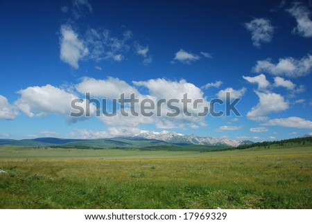 The summer landscape view with mountains and cloudy sky