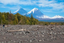 The summits of two volcanoes against the background of the taiga: Gorely Volcano and Mutnovsky volcano. Russia. Kamchatka