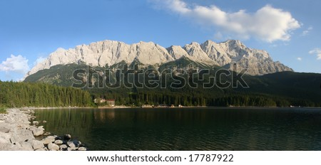 The summits of Zugspitze (right, 2963m) and the Waxensteine (left, 2277m) in the german Alps near Garmisch-Partenkirchen. In the foreground the beautiful lake Eibsee.