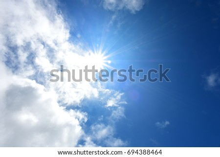 The sun and blue sky background with white clouds  - Shutterstock ID 694388464