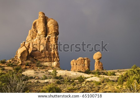 The sun breaks out over Arches National Park after a rainstorm passes over. Dark clouds and the Balanced Rock formation are seen in the background.