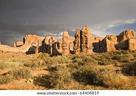 The sun breaks out over Arches National Park after a rainstorm passes over. Dark clouds in the background.