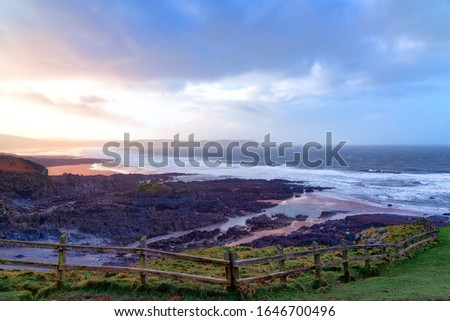 The sun breaks through storm clouds, a wooden fence in the foreground leads the eye down to the beach where  waves break on the beach and rocks. The headland of Baggy Point hazy in the background