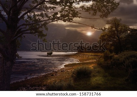 The sun breaks through the heavy cloud hanging over Loch Leven in the Highlands of Scotland.