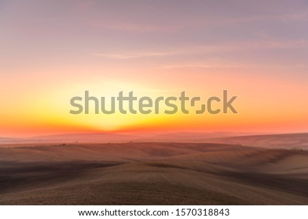 The sun caught during the last moment before setting beyond the horizon with view of a field covered with fog and the farms and fields undulating in the region of South Moravia is also called Tuscany