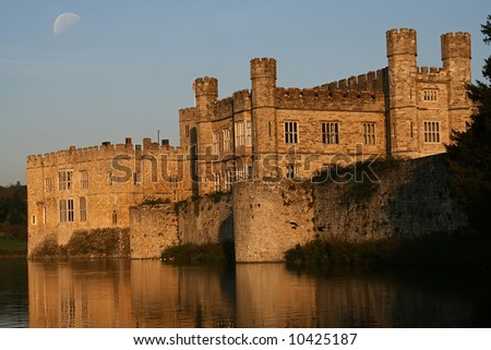 the sun doing down on Leeds castle with moon in the sky
