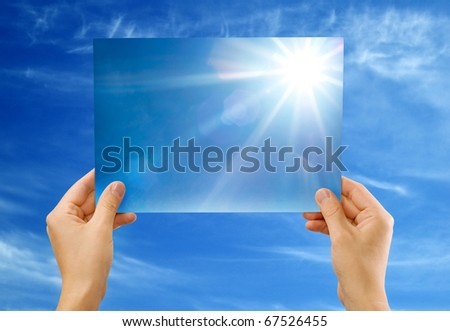 The sun image in hands against the sky