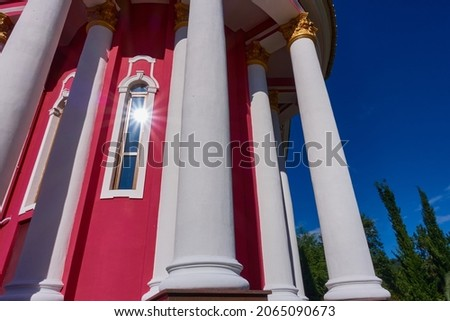 The sun is reflected in the window of a red church with white columns against a background of blue sky and trees.
