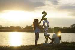 The sun is setting and two children are playing with the number 2021 of golden balloons in the happy park. happy new year 2021.