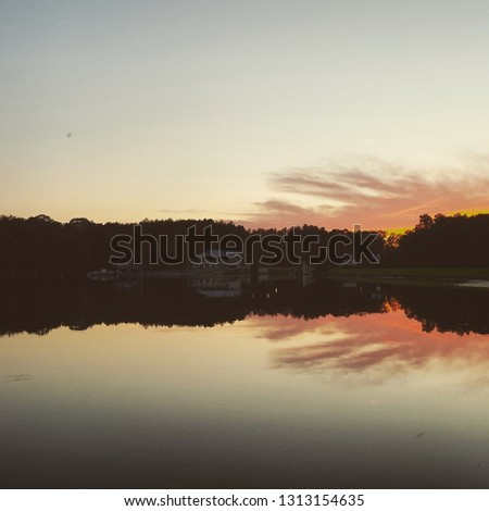The sun is setting on a lake near a campground.  The reflection of the clouds and the forest are in the lake - the dark is starting to creep into the picture.