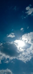 The sun is shining behind the clouds. Beautiful cloudy sky background. Sun breaking through the clouds. Big or tiny and soft clouds with sunlight. Elegant view of sky. Vertical photo