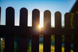 The sun is shining through the fence. Evening in the village. Wooden fence made of boards. Fence around the house.