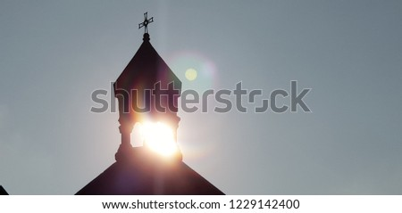 The sun rays breaks through the dome of the church. A beautiful picture.Cross of church against blue sky.