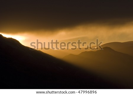 the sun rays cut through the mountains at sunset