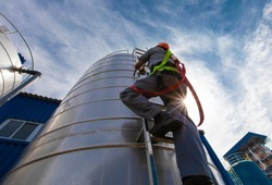 The sun rays through of Climb the ladder worker height safety inspection of thickness storage oil and gas tank industry, concept worker high building outdoors wear equipment protective.