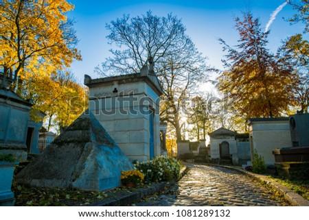 The sun rises above famed cemetery Père Lachaise in Paris, France during autumn #1081289132