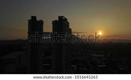 the sun rises behind the yellow cloud buildings #1016645263