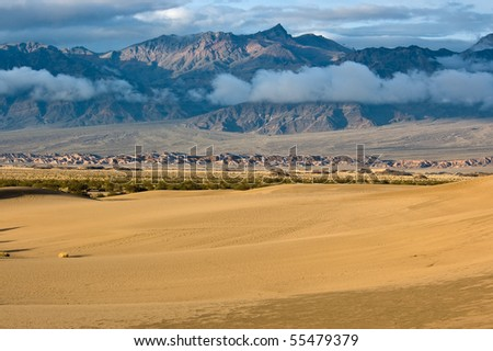 The sun rises on Mesquite Flat Sand Dunes under layers of sunlit mountains and clouds in Death Valley National Park, California.
