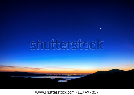 The sun rises on the San Luis Reservoir and Central Valley of California with Venus still in the night sky.