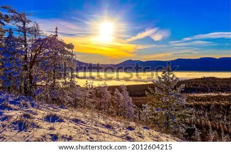 The sun rises on the snowy peaks. Winter dawn in mountains. Winter sunrise at dawn. Winter dawn