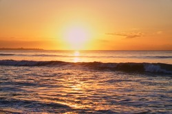 The sun rises over the horizon at the dawn of the sea. Ocean at sunset. Sandy blyaz and a wave on the seashore. High quality photo