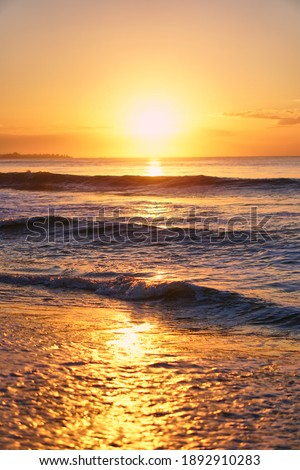 The sun rises over the horizon at the dawn of the sea. Ocean at sunset. Sandy blyaz and a wave on the seashore. High quality photo Photo stock ©