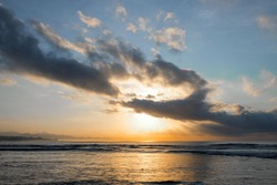The sun rises over the ocean with backlit clouds. Beautiful sunrise at Pantai Pabean Ketewel Beach on the east coast of Bali.