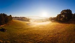 The sun rises thru fog on a cold autumn morning near Kangaroo Ground in the Yarra Valley, Victoria, Australia