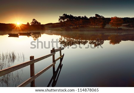 The Sun rising over a calm Knapps Loch, with a wooden fence leading in to the water and tree reflections in the distance. Scotland