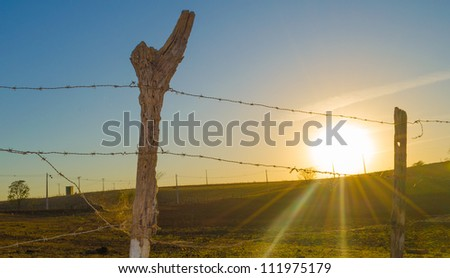The sun rising with a wood and barbed wire fence in the foreground