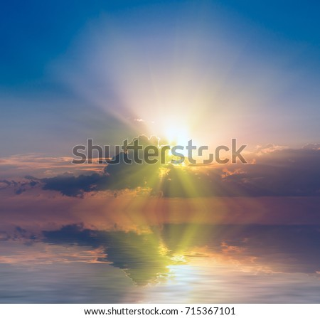 The sun's rays are visible from the clouds at dawn over calm water. Natural sunset composition #715367101