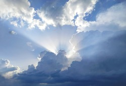 The sun's rays behind the cumulus clouds