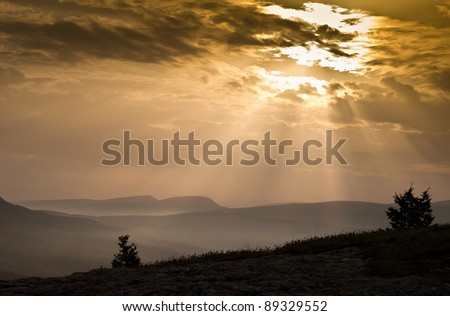 the sun's rays make their way through the clouds in the mountains