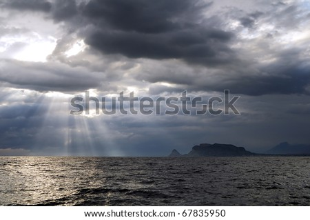 The sun's rays passing through the storm clouds over the sea