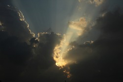 The sun's rays protrude through the clouds