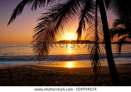 The sun sets behind a little island in Playa Carrillo, Costa Rica.