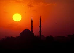 The sun sets behind a silhouetted mosque in Istanbul, Turkey
