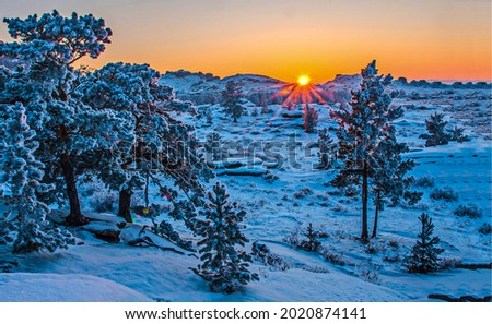 The sun sets behind a snowy hill. Sunset winter mountain. Sunset in winter snow mountains. Snowy mountain at sunset