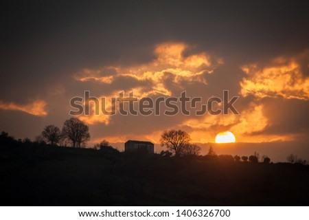 the sun sets behind the farm at the top of the hill #1406326700