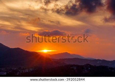 The sun sets behind the mountains over the jungle in the tropics\n
